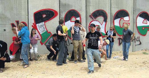 """Politische Grafitti-Aktion: Gemeinsam mit zwölf Jugendlichen aus dem Münchner Umland sprüht der Hip-Hop-Künstler Enz (im Bild vorne) """"no peace without dignity"""" auf die Grenzmauer in der Westbank..."""